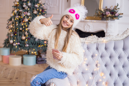Little girl gesticulating ok and smiling at the Christmas tree background. Stylish and fashionable clothes. Merry Christmas and Happy Holidays!