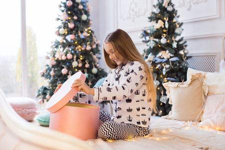 Merry Christmas and Happy Holidays! Christmas presents, kid and holiday concept. Beautiful girl opens a Christmas gift from Santa Claus