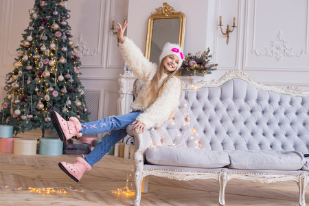 Little girl gesticulating ok and smiling at the Christmas tree background. Stylish and fashionable clothes. Merry Christmas and Happy new year! Banco de Imagens