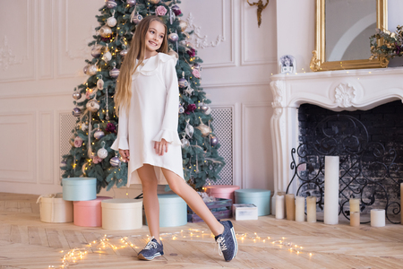 Merry Christmas and Happy Holidays! Beautiful child in beautiful dress on the background of a Christmas tree. Stylish and fashionable wears. Banco de Imagens