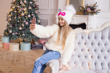 Little happy girl is doing selfie with christmas tree. Merry Christmas and Happy Holidays! Stylish and fashionable clothes.