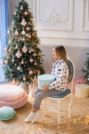 Christmas Concept - Little happy girl sits on a background of Christmas decorations with a gift and smiles. Merry Christmas and Happy new year! Banco de Imagens