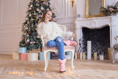 Little happy girl sits on a background of Christmas decorations in stylish and fashionable clothes