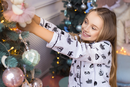 Beautiful happy smiling girl is decorating the Christmas tree indoors. Concept of preparation for the new year. Banco de Imagens