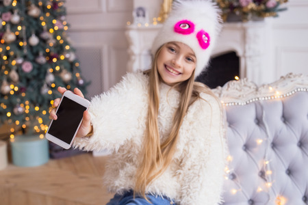Little girl shows blank phone screen. Stylish and fashionable clothes. Merry Christmas and Happy Holidays!