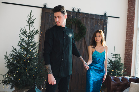 Beautiful elegant couple of lovely man and girl hold handsome look away. Christmas atmosphere in the home location. Scandinavian interior with a Christmas Tree. Banco de Imagens - 91398889