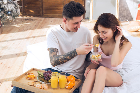 Beautiful couple in love feeds each other. Healthy Eating. Healthy breakfast in bed. Couple celebrating Christmas together.