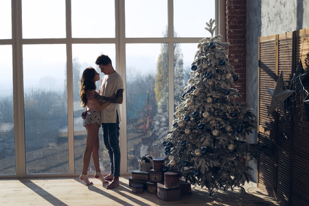 Lovely couple hug together and smile to each other. Sexy girl and boy. Couple celebrating Christmas together. Banque d'images