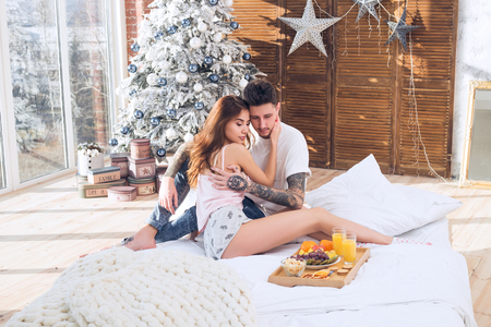 Beautiful romantic couple. Healthy breakfast in bed. Couple celebrating Christmas together. Love is the best gift. Happy New Year and Merry Christmas Banco de Imagens - 91335364
