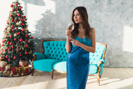 Beautiful elegant girl drinking wine at the Christmas near Christmas Tree in beautiful blue dress. Smiling sexy and attractive girl with beautiful hair on the Christmas party Banco de Imagens - 91398918