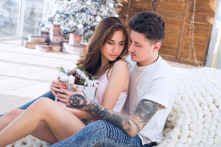Beautiful couple sitting and hug together. Boyfriend gave the girlfriend flowers. They sit on the background of a New Year tree. Banco de Imagens