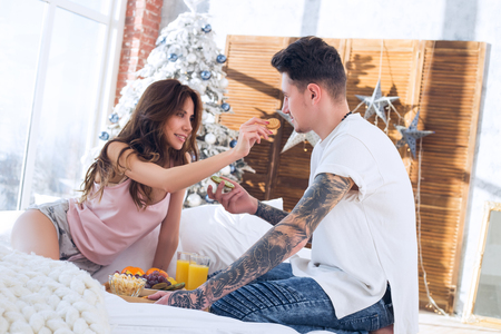 morning, healthy breakfast, couple, christmas- concept. Couple celebrating Christmas together. Happy young couple drinking juice and eating fruits and enjoying Christmas morning.