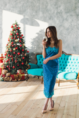 Beautiful elegant girl drinking wine at the Christmas near Christmas Tree in beautiful blue dress. Smiling sexy and attractive girl with beautiful hair on the Christmas party Banco de Imagens