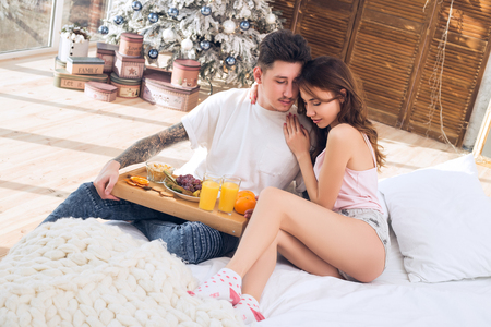 Beautiful romantic couple. Healthy breakfast in bed. Couple celebrating Christmas together. Love is the best gift. Happy New Year and Merry Christmas
