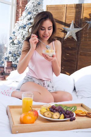 Healthy Eating Woman. Delicious Berries And Crunchy Cereal In Morning. Breakfast. Christmas background Banco de Imagens