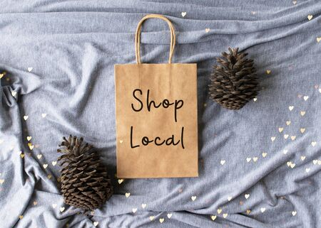 Shop Local text on a plain brown paper bag flat lay - Christmas winter scene