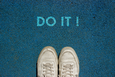 New life concept, Sport shoes and the word DO IT ! written on walk way ground, Motivational slogan.