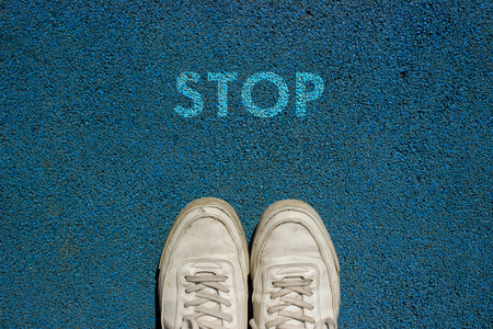 New life concept, Sport shoes and the word STOP written on blue walk way ground, Motivational slogan.