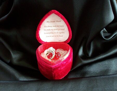 Ring and roses in heart box on black.