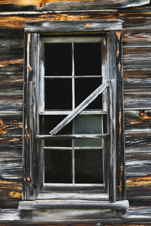 getting away from it all: Rustic old barn window with broken glass