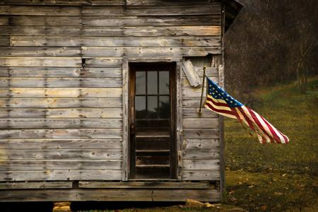 Drapeau américain suspendu à une ancienne grange avec espace négatif pour afficher le texte. Banque d'images
