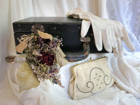 goodies: A collection of goodies: vintage suitcase, full length gloves, beaded purse, and dried flower bouquet.