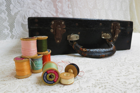 needlecraft product: Vintage thread spools with colorful thread, with a tailors kit suitcase, against ivory white lace. Stock Photo