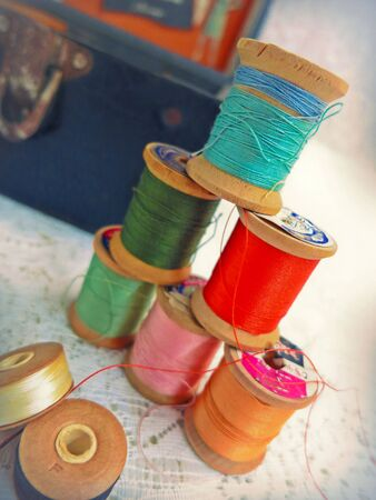 old spools: From a mid-century tailor kit, old wood spools with thread, stacked into a pyramid.