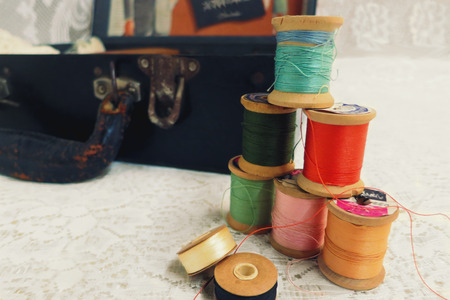 needlecraft product: Vintage thread spools with colorful thread, with an opened tailors kit suitcase, against ivory white lace.
