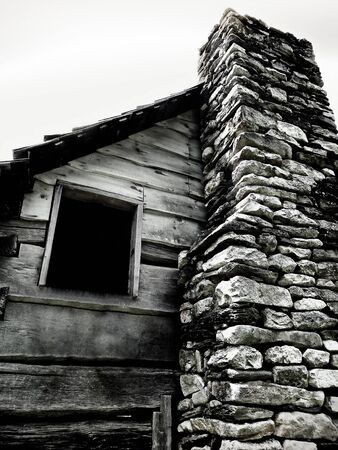 woodshed: Empty cabin window, with stone chimney, in a monochrome finish. Stock Photo