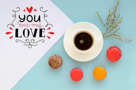 St Valentines Day vintage overhead composition of note with love confession, macarons and coffee mug on tender blue background