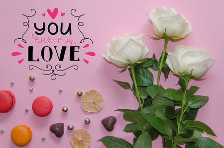 St Valentines Day vintage composition of white roses, macarons, chocolate hearts and hand drawn love quote on pink background Stock Photo