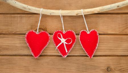 trabajo manual: Romantic love composition of red felt hearts on wooden background Foto de archivo