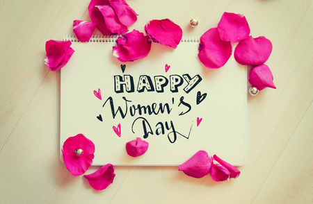 International Women's Day vintage composition of greeting note with hand drawn lettering and rose petals on wooden table. 8 March greeting card