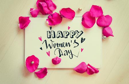 Composizione epoca Giornata internazionale della donna di nota auguri con disegnata a mano lettering e petali di rosa sul tavolo di legno. 8 marzo biglietto di auguri Archivio Fotografico