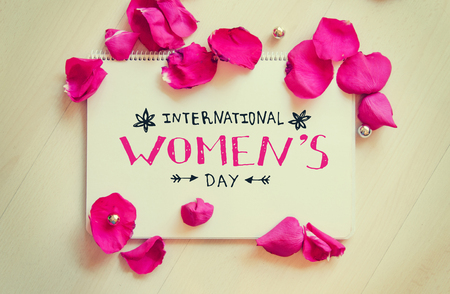International Womens Day vintage composition of greeting note with hand drawn lettering and rose petals on wooden table. 8 March greeting card Stock Photo