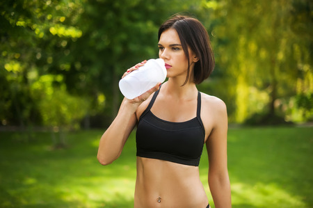 the woman drinks the water and enjoy the summer sun after a workout