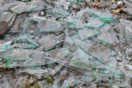 Shards of broken glass on the ground, textured background, closeup