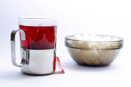 cup of fruit tea and a pot with sugar cubes Stock Photo