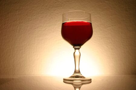 A glass of red drink with soft light and textured background photo