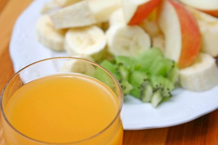 orange juice and fruit on a plate