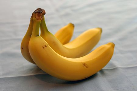 bananas on table cloth with bread crums and visible cloth texture