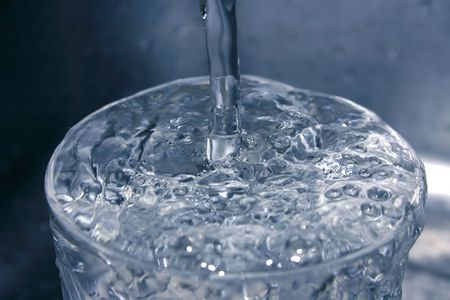 glass of running water in almost monochromatic tones Stock Photo