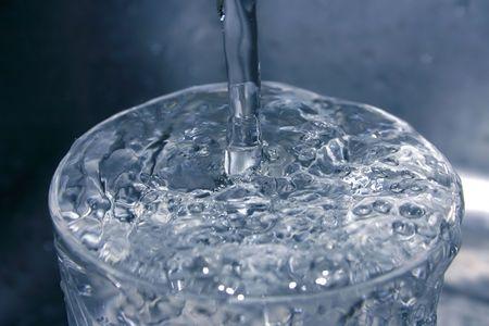 szklanką wody bieżącej w niemal monochromatycznej dzwonka Zdjęcie Seryjne