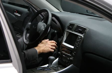 mans hand in new car interior, man wearing a business suit Stock Photo