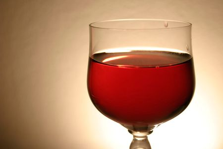 A glass of red drink with soft light and textured background