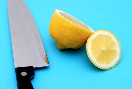 kitchen knife with sliced lemon on blue background