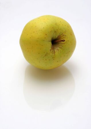 yellow green apple on reflective surface