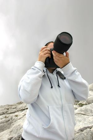 woman taking photograph against dark cloudy mountain sky Stock Photo - 529363