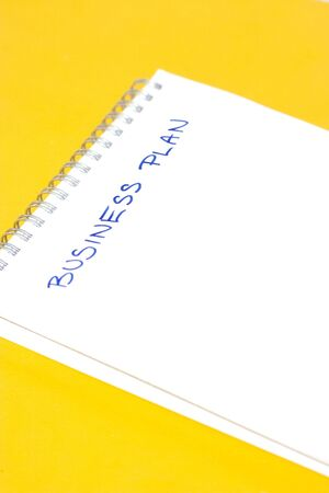 business plan title on empty sheet of white paper, yellow background
